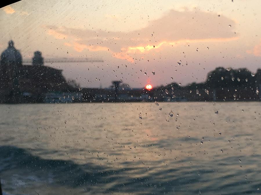 Sonnenuntergang über Venedig, durch gischtbespritzte Fenster des Vaporetto hinaus. Ein Glutball, der hinter den Palazzi versinkt. Wunderschön!