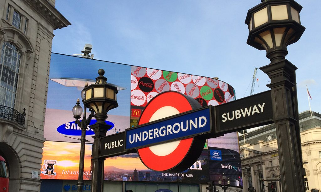 Das typische Londoner Underground-Zeichen, roter Ring mit blauem Balken, hier am berühmten Piccadilly Circus.