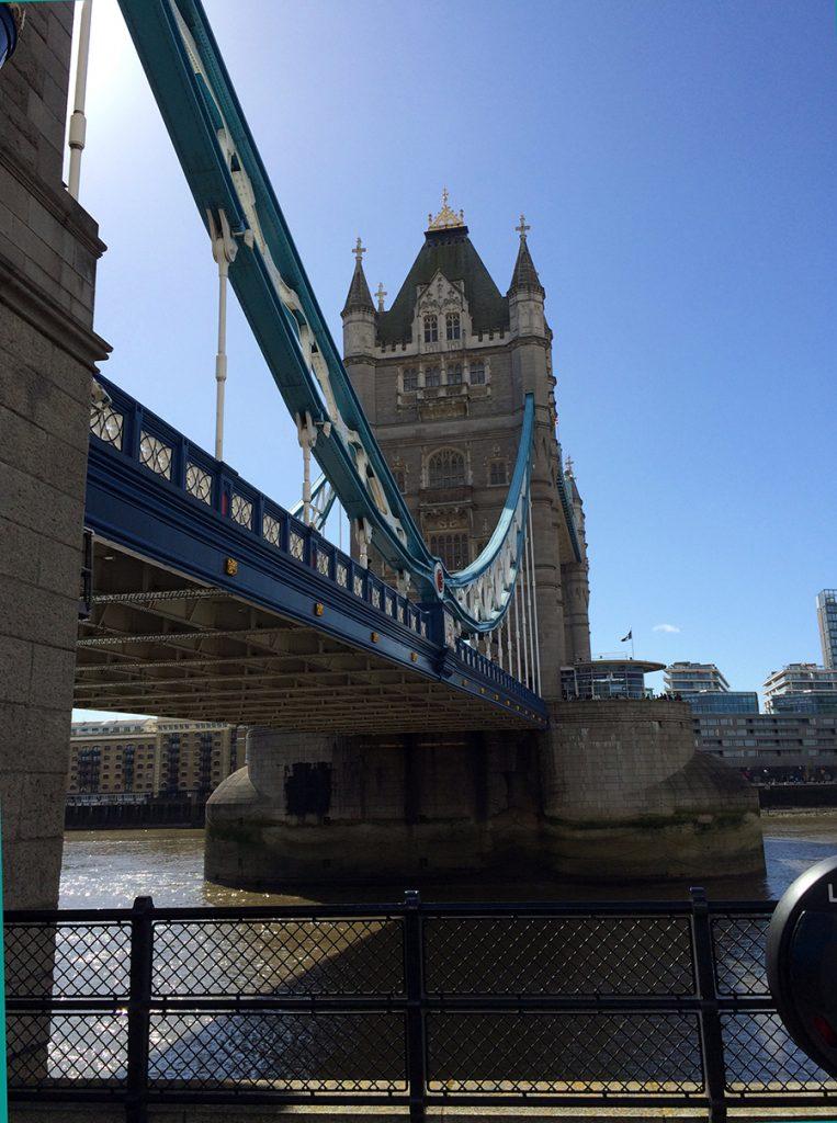 Sicht von der Promenade vor dem Tower auf den Nordturm der Tower Bridge vor einem typisch strahlenden, blauen, britischen Himmel.