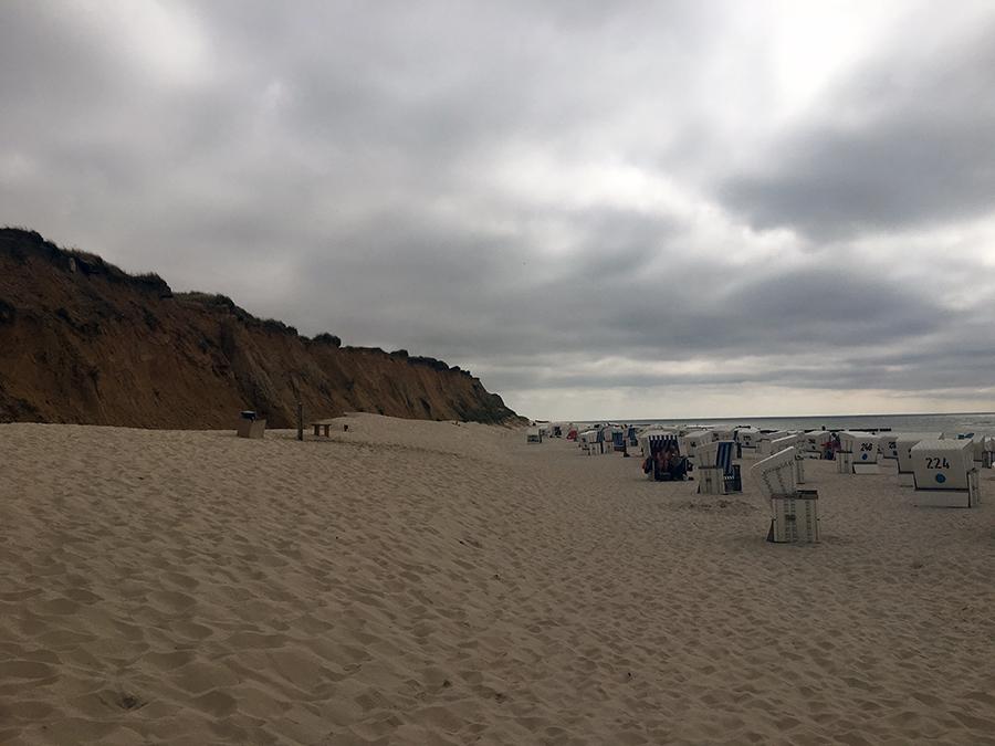 Links das Rote Kliff am Strand von Kampen, rechts die typischen weißen Strandkörbe und das Meer.