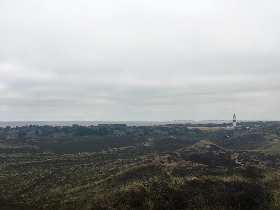 """Blick von der Uwe Düne auf die Landschaft, hinten der """"Lange Christian"""", Kampens weißer Leuchtturm mit schwarzem Band."""
