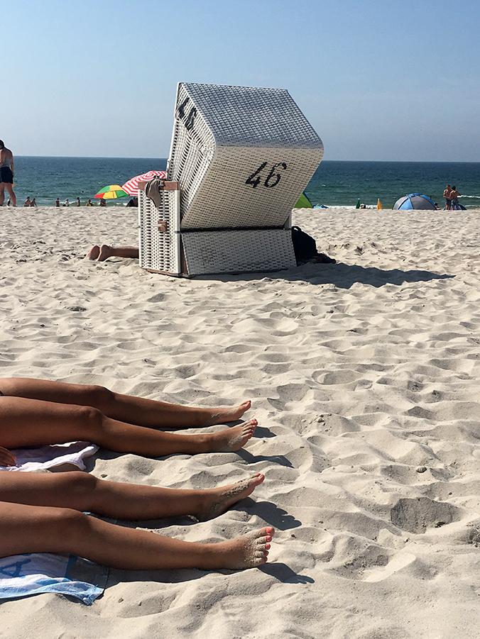 Die Farben Sylts: Nordseeblaues unendliches Meer, mattblauer Himmel, zartbeiger Sand, der nur hier ganz genau diese Farbe zu haben scheint, strahlendes Weiß für die Standkörbe und noch ein kleiner Klecks Schwarz für die Nummern hintendrauf. Und dazu braungebrannte Beine!