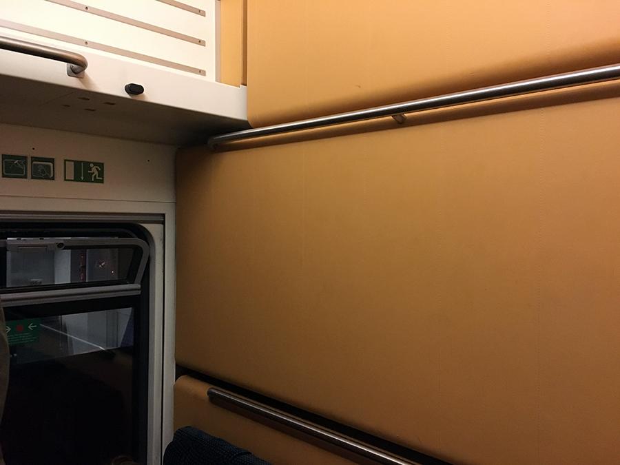 Ein Blick in unser Abteil: Ein gekipptes Fenster und noch hochgeklappte Betten. Direkt unten davor unsere Sitze.