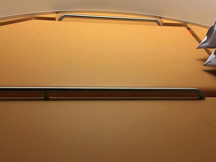 Das mittlere und das obere Bett unter der Decke, noch hochgeklappt. Rechts luken die Kopfkissen auf der Ablage über der Abteiltür hervor.