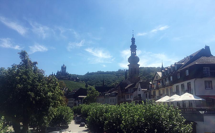 Die schönen Häuser an einer Allee in Cochem am Moselufer und im Hintergrund die Reichsburg.