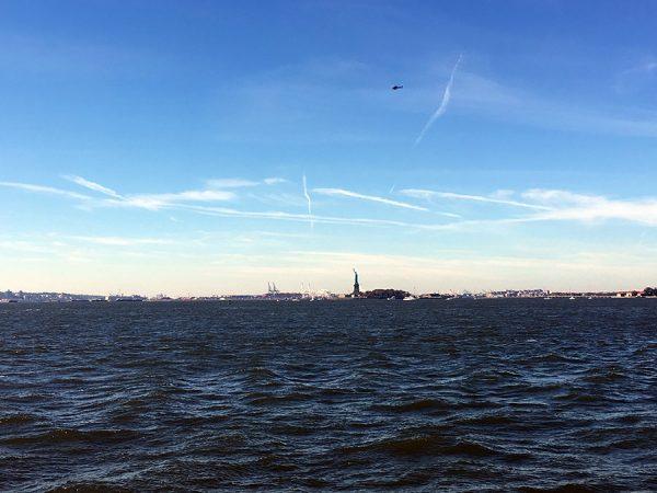Ziemlich weit weg, die Freiheitsstatue, von unserer Bank am Pier.