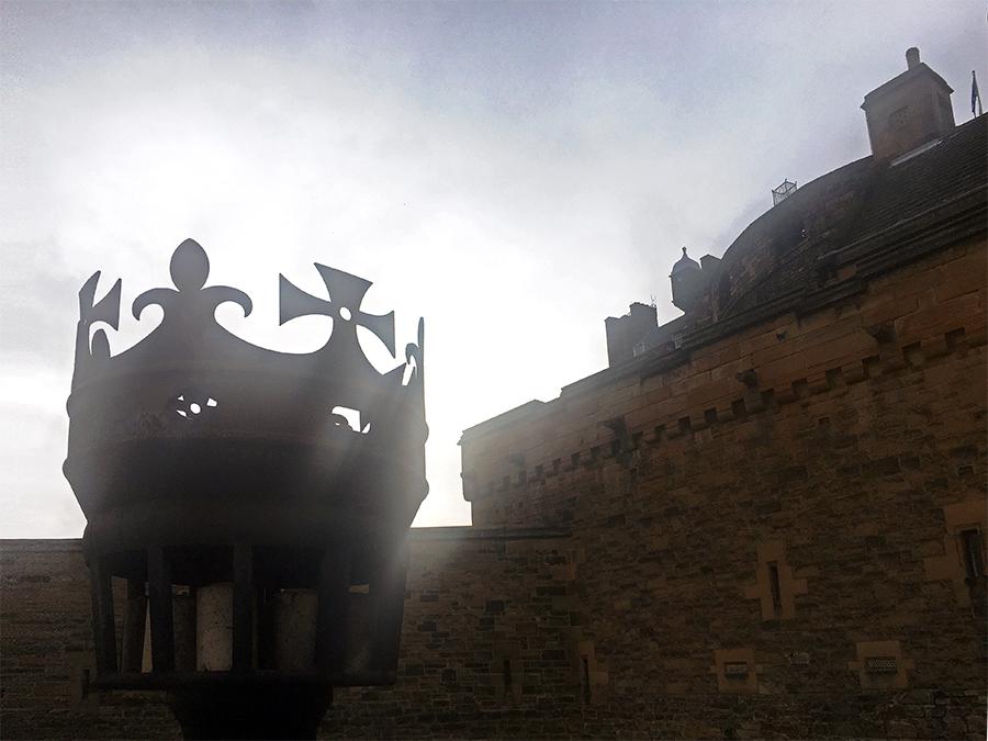 Eine alte Fackelhalterung vor der Burg im abendlichen Gegenlicht.