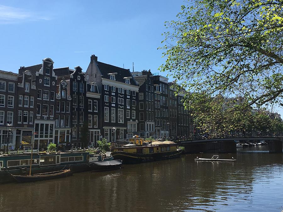 Giebelhäuser an einer Gracht samt Hausboot und Brücken - das ist wirklich typisch Amsterdam!