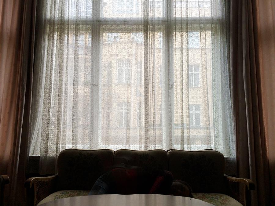 Große Fensterfront über klassischem Sofa und Spitzengardinen zur Fasanenstraße hin.