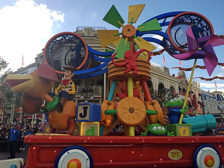 Buzz Lightyear und Woody folgen auf einem quietschebunten Spielzeugwagen für Toy Story.