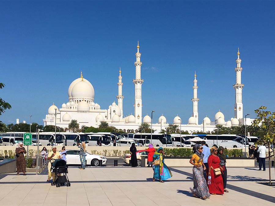 Elegant gekleidete Frauen in fließenden Gewändern und mit Kopftuch vor der Scheich-Zayid-Moschee.