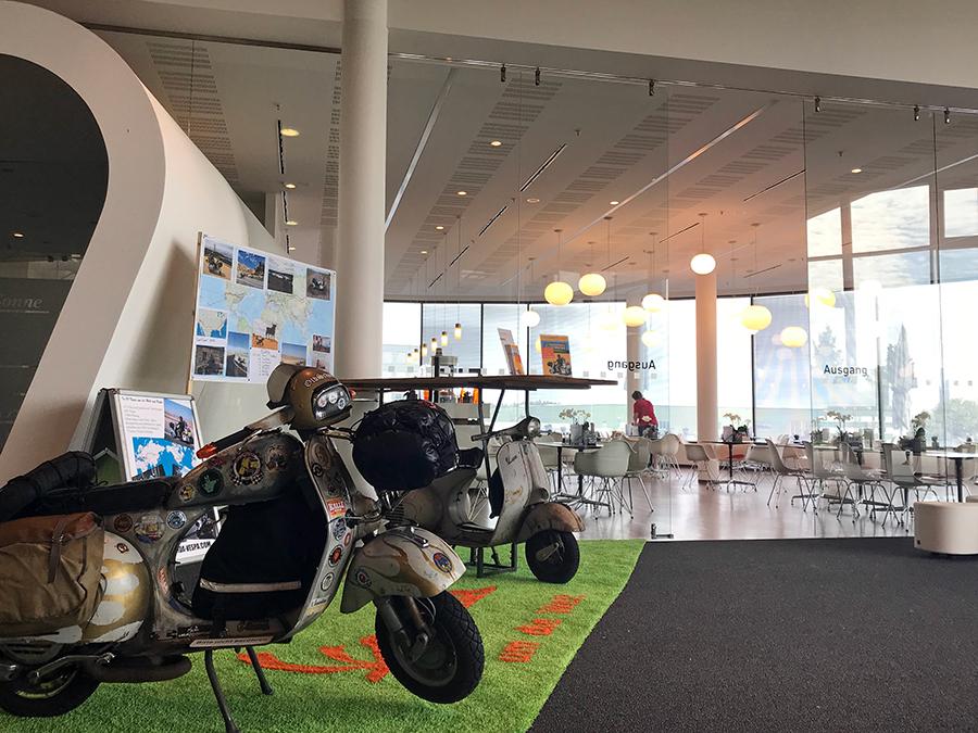 Schon in der Eingangshalle des Erwin-Hymer-Museums sind ein paar weitergereiste Motorräder zu bestaunen, im Hintergrund das Restaurant.