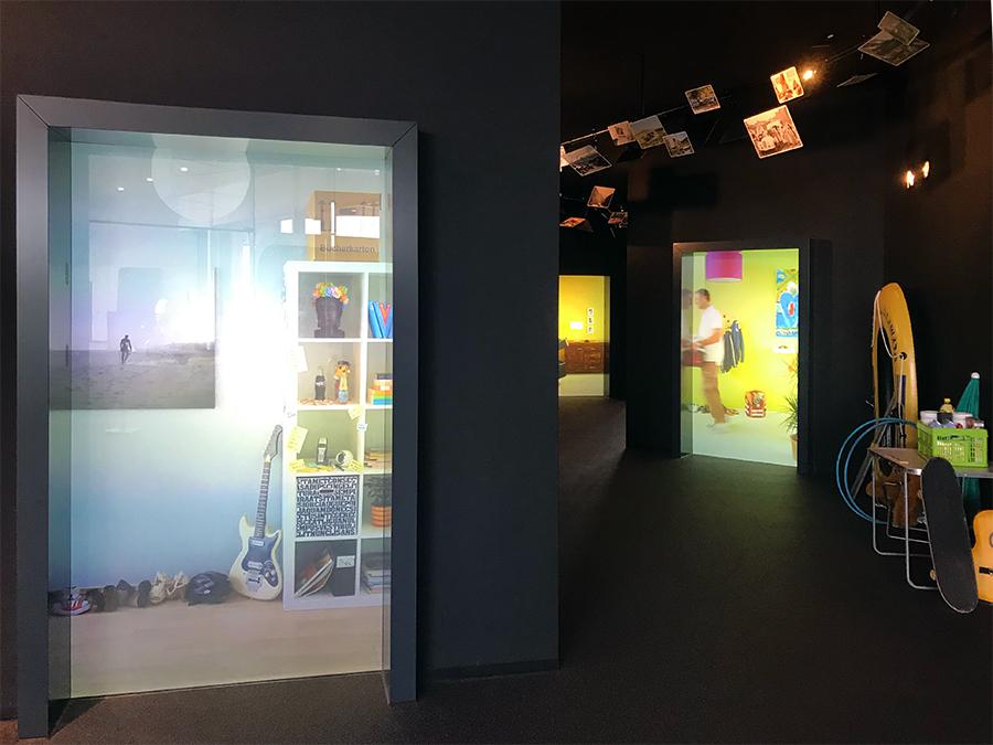 Der Weg in die Ausstellung führt durch einen Gang, in dem Video-Szenen Einblick in Urlaubsvorbereitungen geben. Cool!