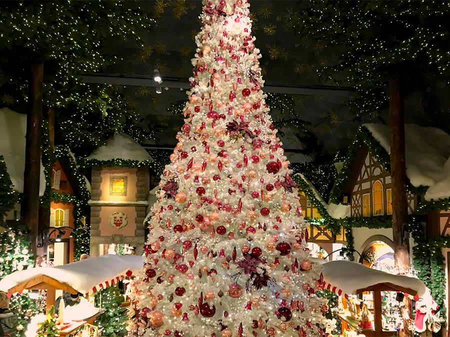 Ein riesiger, weißer, reich geschmückter Kunsttannenbaum steht in der Mitte des zentralen Raumes in Käthe Wohlfahrts Weihnachtsladen.