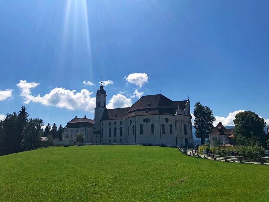 Auf einer kleinen Anhöhe, nur wenige Schritte vom Parkplatz entfernt, liegt sie: Die Wieskirche in Steingaden.