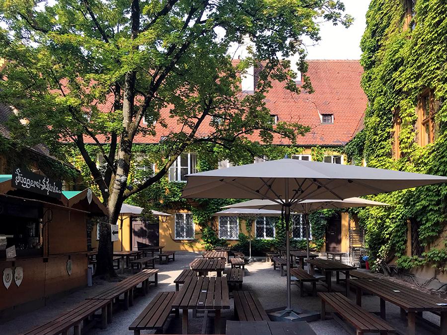 Der lauschige Biergarten in der Fuggerei in Augsburg, direkt rechts hinterm Eingang.