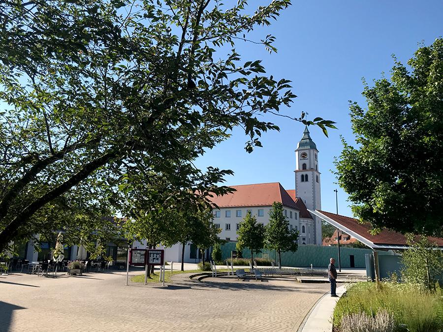 Vor dem Kurhaus von Bad Wurzach ist viel Platz für Kurkonzerte, mit Blick auf die Kirche St. Verena.