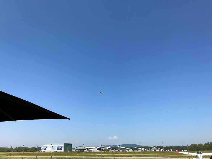 Oben in der Luft setzt gerade ein Flugzeug zum Landen an, und unten am Boden macht sich ein Zeppelin startklar.