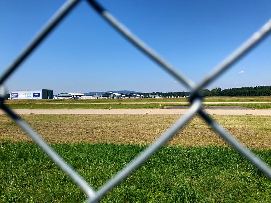 Blick durch den Zaun zum gegenüberliegenden Hangar des Flugplatzes von Friedrichshafen.