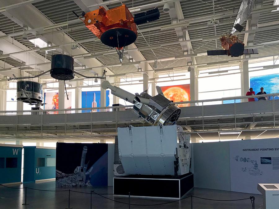 Unter der Decke des Hangars hängen Satelliten und Sonden aus der Raumfahrtabteilung aus dem Stockwerk darüber.